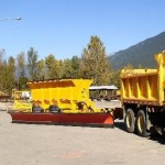 A tow plow being pulled behind a plow truck