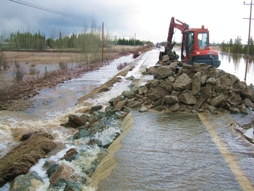 An excavator adds rock to the shoulder of a roadway to protect it from flood damage.