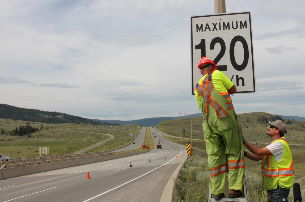 Crew installing speed limit sign on a highway