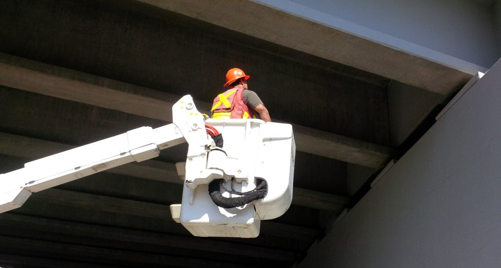Bridge inspector inspecting a bridge, in a utility bucket truck