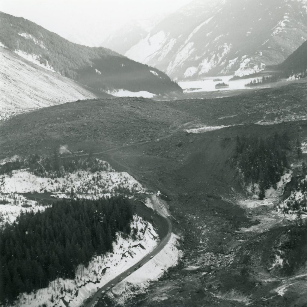 A line of cars parked along BC Highway 3 at the western edge of the slide site and the vast scope of the debris field is revealed.