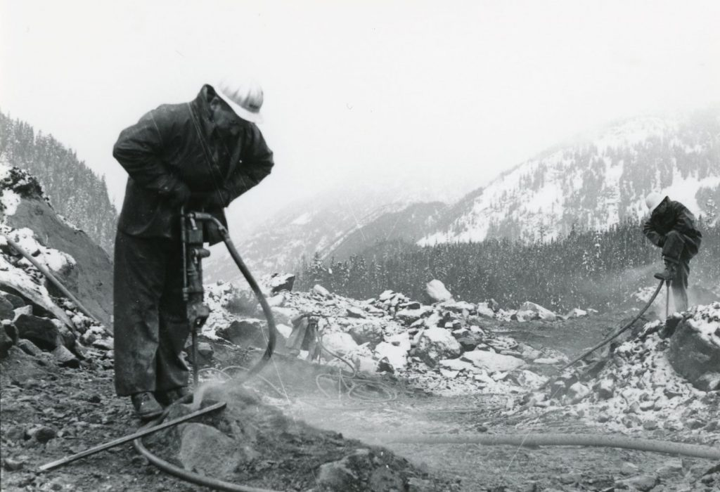 Ministry staff drilling to clear a new route through the slide site on BC Highway 3.