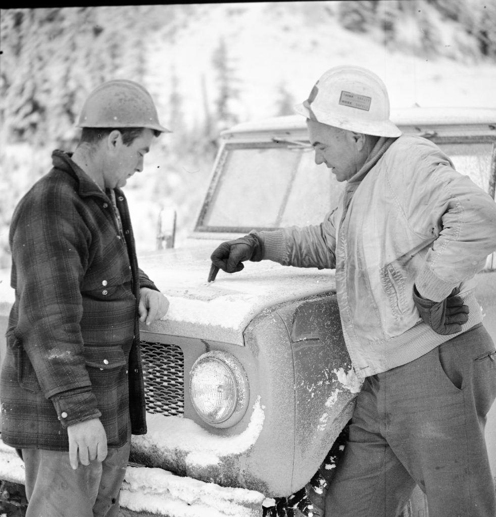 Staff use snow on the hood of a truck to draw plans during recovery.