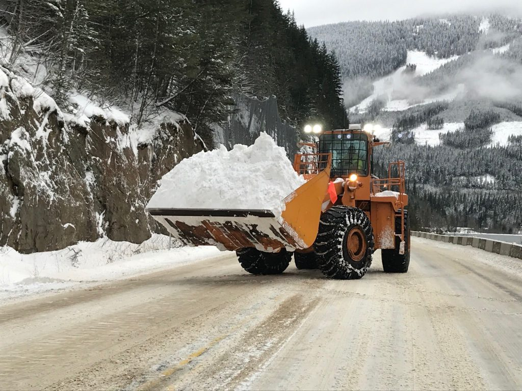 Front-end Loader with snow bucket clearing snow from a BC highway.