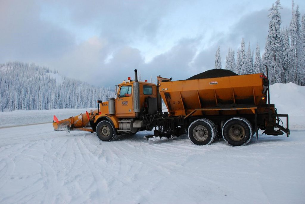 A front plow with an aggregate hopper on the back to dispense sand, gravel or de-icing materials to apply extra traction to the road after plowing.