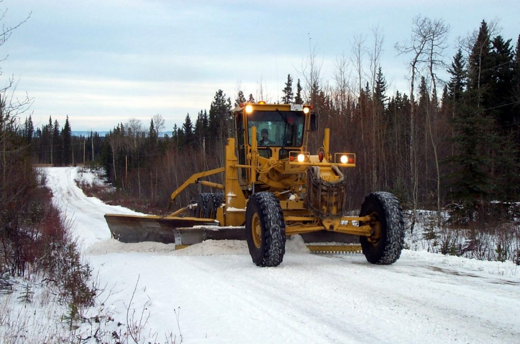 A grader with an under body plow working on clearing a rural road.