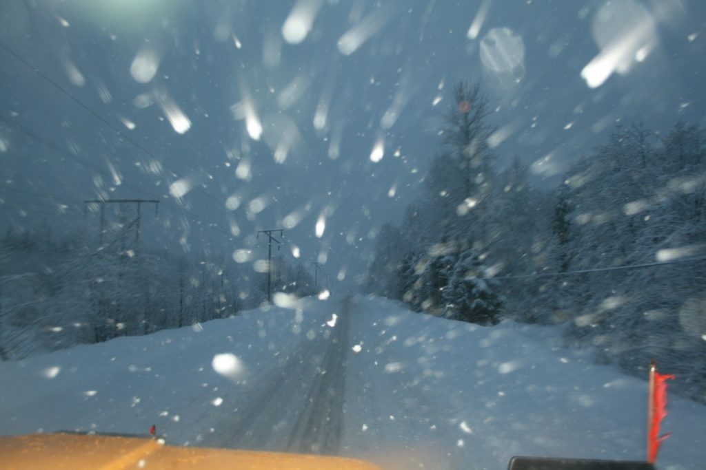 A snapshot taken from the front of a plow at work during a snowstorm on a BC highway.