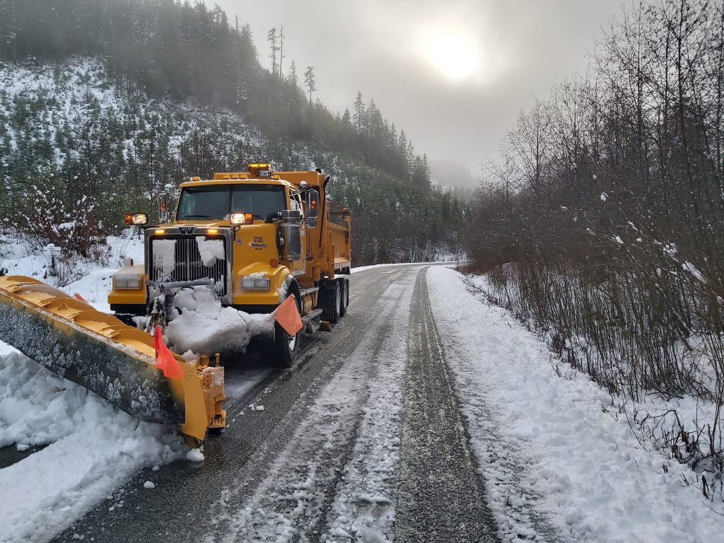 A snow plow clears snow from a BC Highway