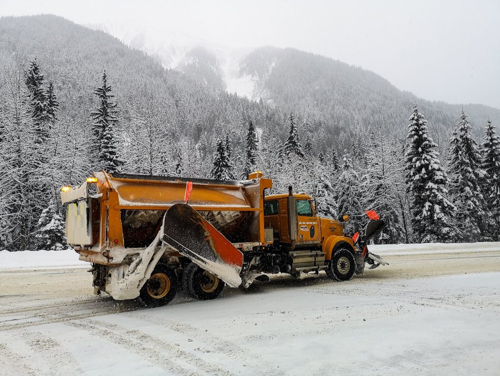 A side view of a plow truck with wing plow, underbody plow, front plow and hopper. Truly a tool for every snow occasion.