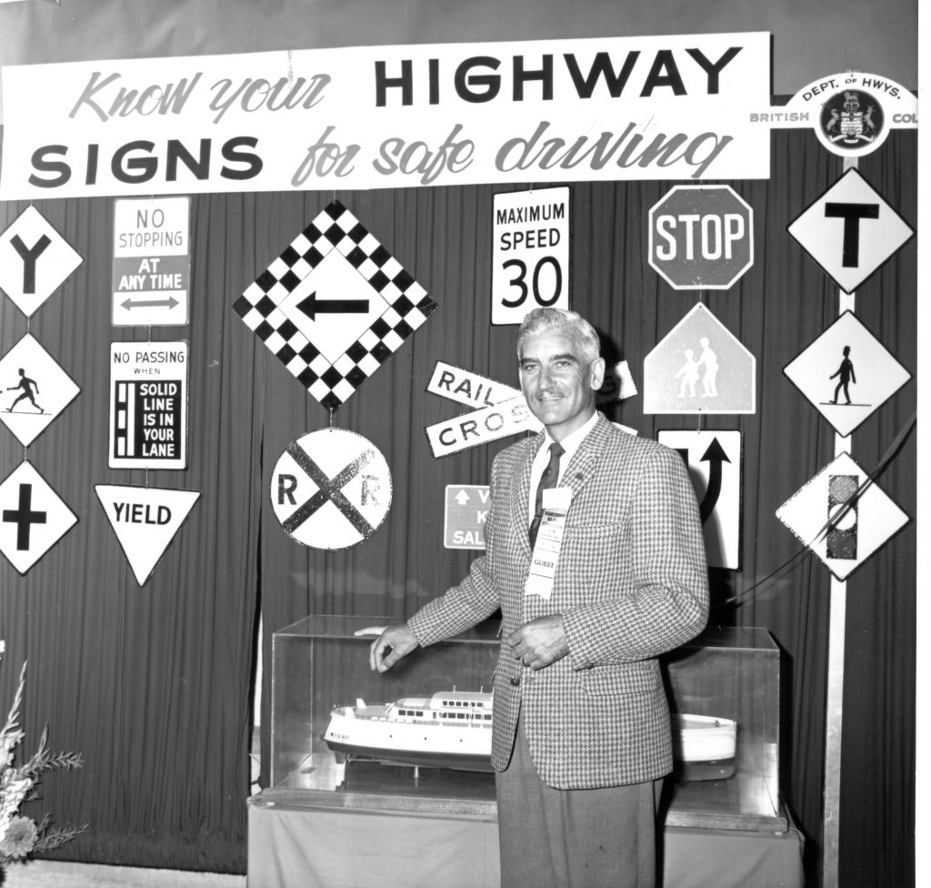 A ministry staffer stands in front of a display of highway information signs, in 1965.