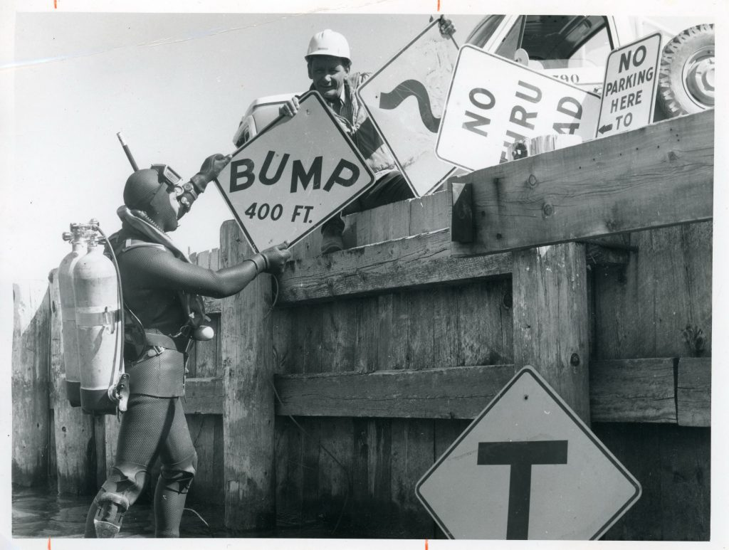 A scuba diver retrieves BC highways signage from Lake Okanagan during the 1960s.