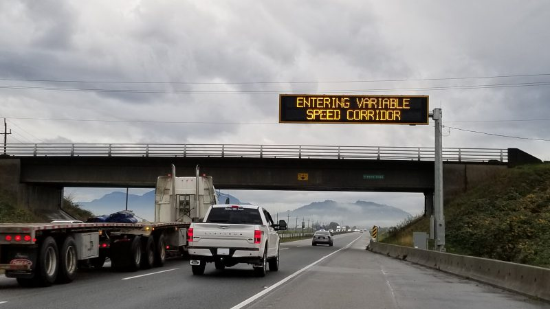 Variable speed sign with trucks driving underneath