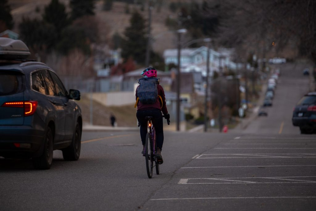Woman cycling with car passing
