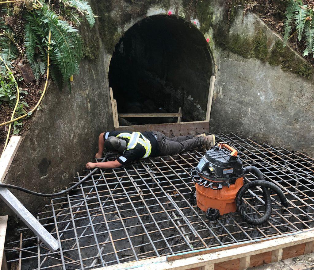 Worker repairing culvert