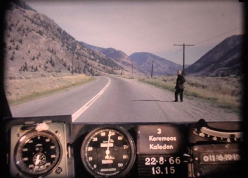 Man in black hitchhiking outside of Keremeos