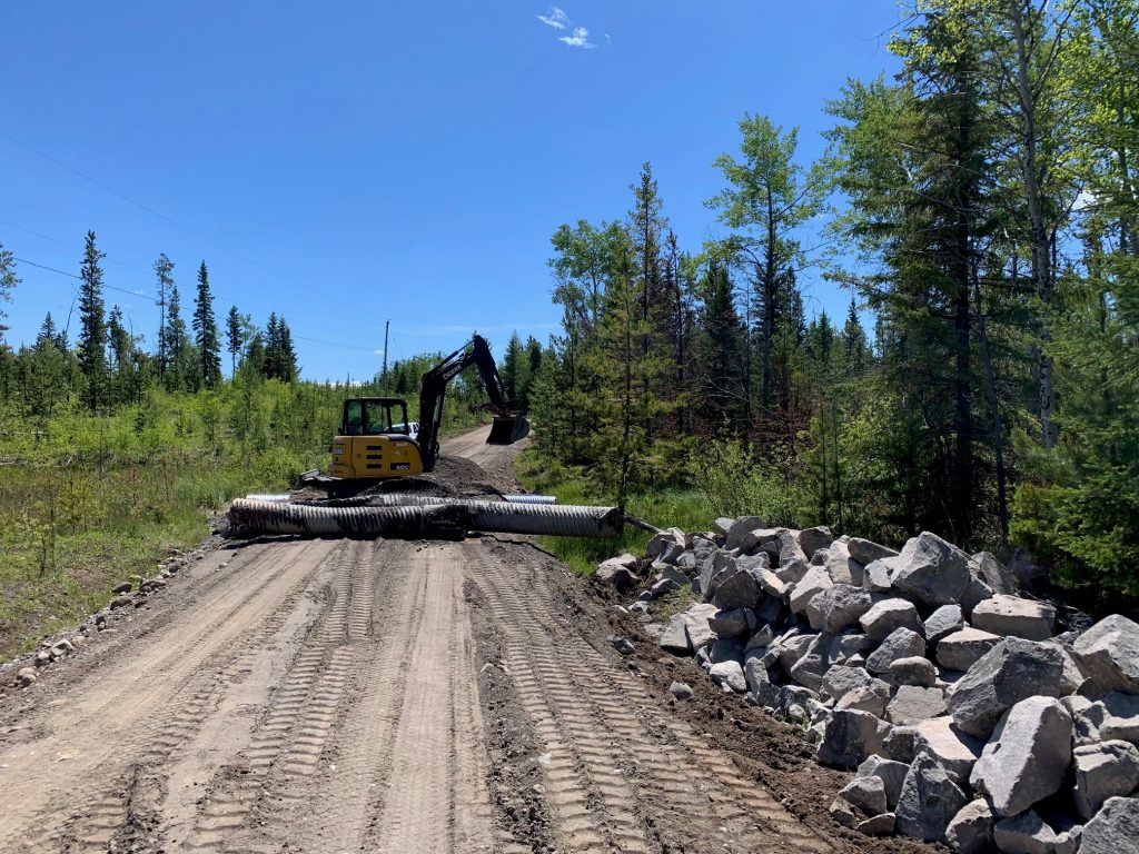 An excavator prepares to install culvert on Taylor Lake Road.