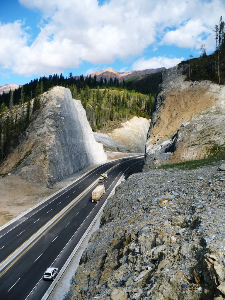 traffic moves through large rock with cut through on the Trans Canada highway near Revelstoke